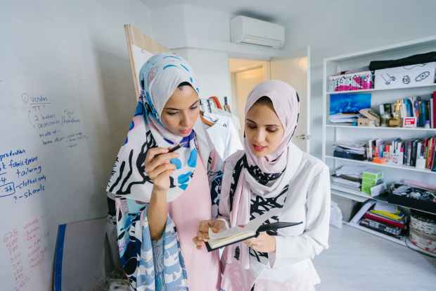 two women in white hijab veils